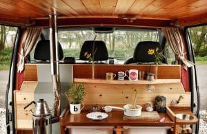 The inside of a self-built campervan including diesel heating, mugs, pans and plants looking out over the front cabin