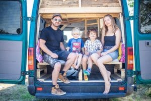 Family with two young children is in the back of their self-built, quirky campervan