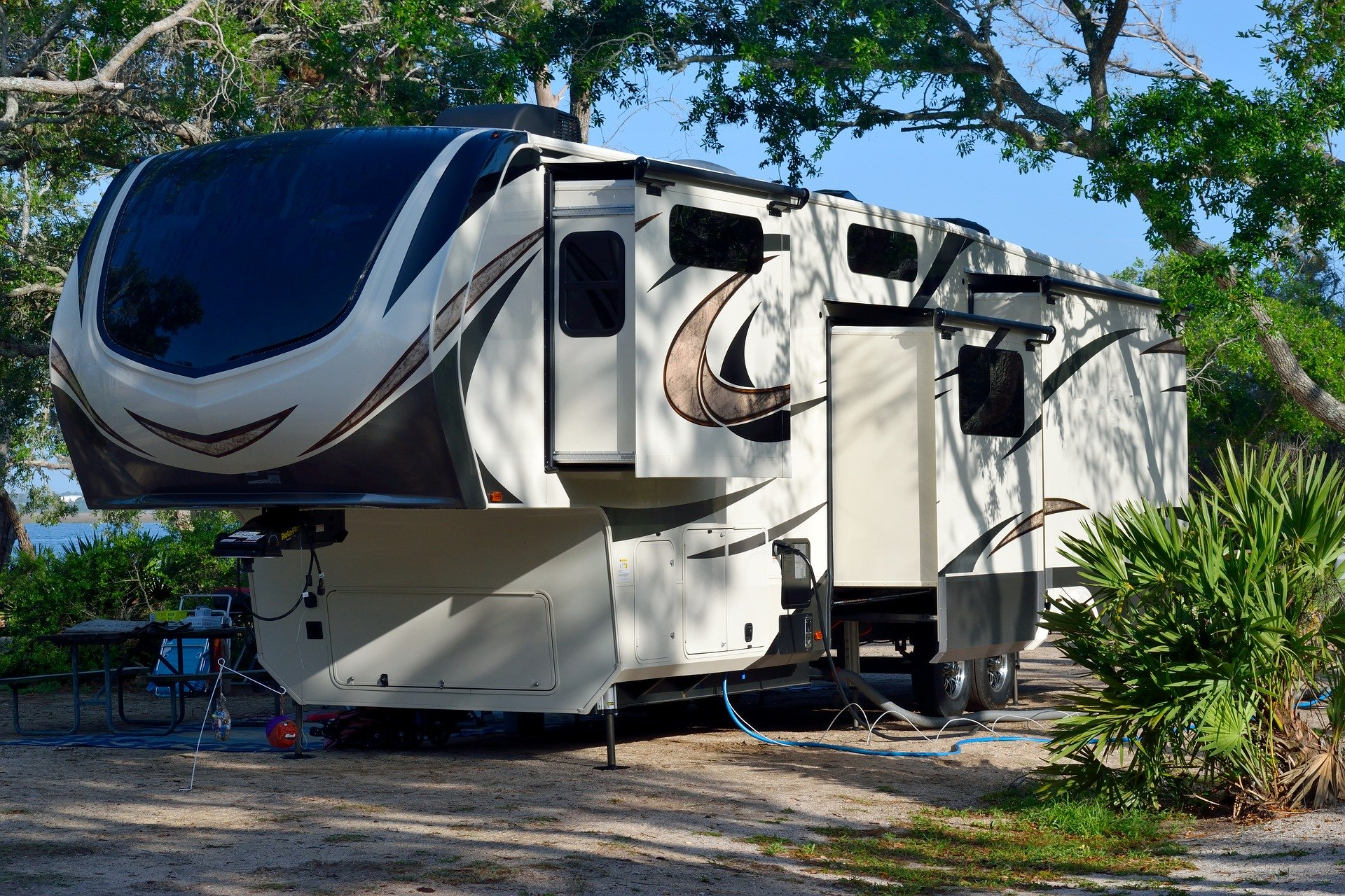 a fifth wheel trailer set up on a campsite